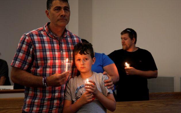 Gavin Kreider, de 9 años, sostiene una vela encendida mientras su padre Durant Kreider lo tiene en una vigilia de oración por las víctimas de un incidente de tiroteo en Virginia Beach. Foto: Reuters
