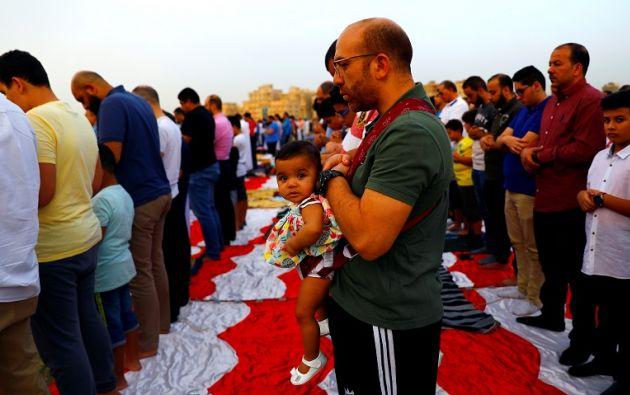 """Un niño reacciona mientras su padre lo lleva durante las oraciones para marcar el final del santo mes de ayuno de Ramadán frente a """"El Aziem"""" (Mezquita de El Grande). Foto: Reuters"""