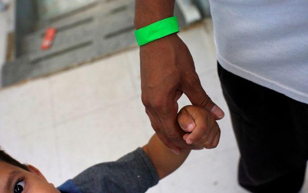 """Un niño centroamericano toma la mano de su padre en el refugio católico """"Iglesia de San Francisco Javier"""". Foto: Reuters"""