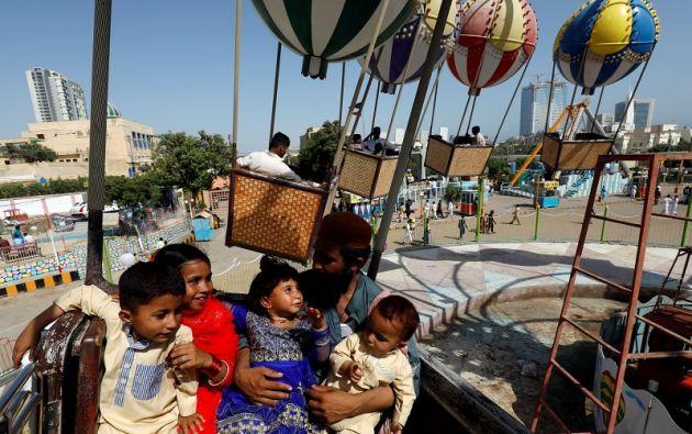 Abdul Karim, de 26 años, padre de cuatro hijos, se sienta con sus hijos mientras viajan en un carrusel, durante el tercer y último día del feriado musulmán. Foto: Reuters