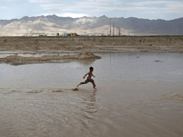 Niño afgano corre en aguas poco profundas para la diversión en las afueras de la ciudad de Kabul. Foto: REUTERS