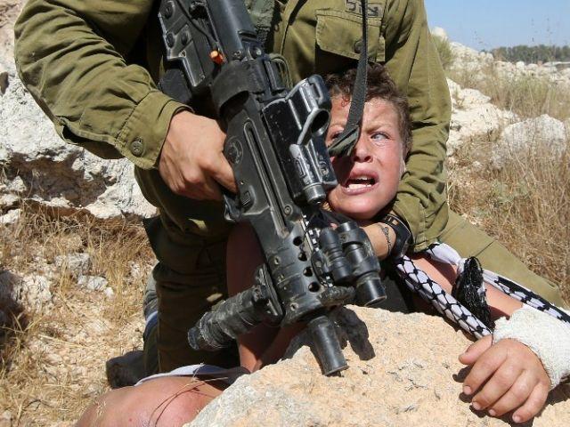 Un soldado armado israelí controla un niño palestino durante los enfrentamientos entre las fuerzas de seguridad israelíes y manifestantes palestinos. Foto: AFP.