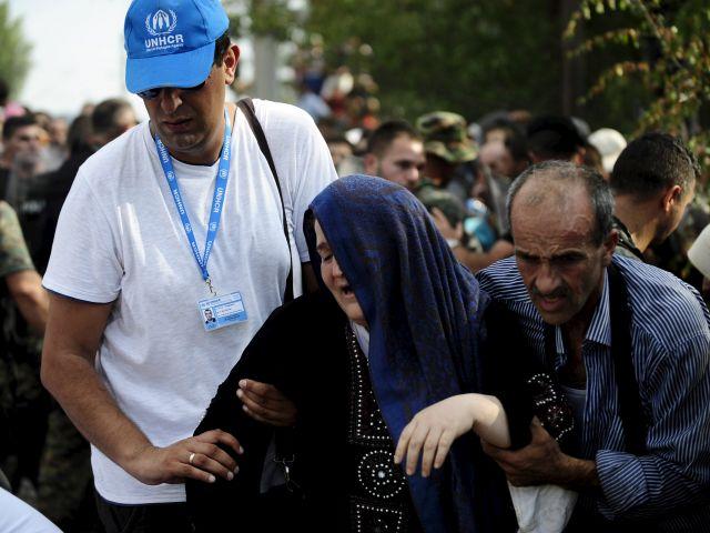Trabajadores de la ONU ayudan a una mujer en la línea fronteriza que divide Macedonia y Grecia. Foto: REUTERS