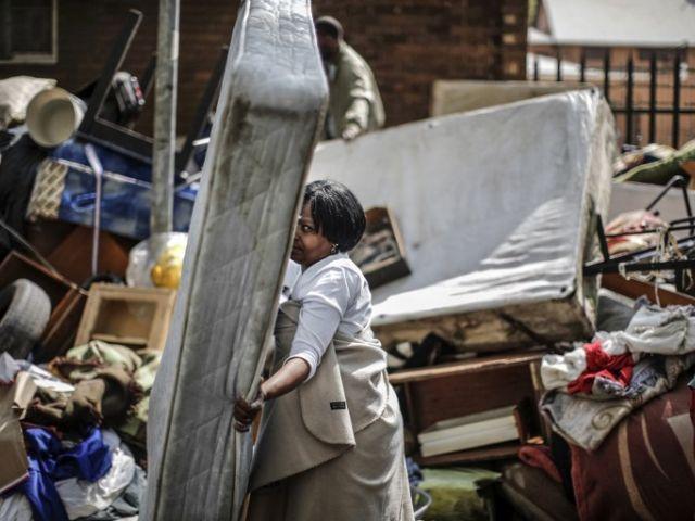Una mujer salva un colchón de un montón de muebles en una calle de la popular distrito centro de la ciudad de Hillbrow. Foto: AFP