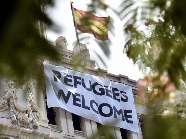 """Una bandera española flamea con la frase """"bienvenidos refugiados"""", frente a la fachada del Palacio de Cibeles, el Ayuntamiento de Madrid. Foto: AFP."""