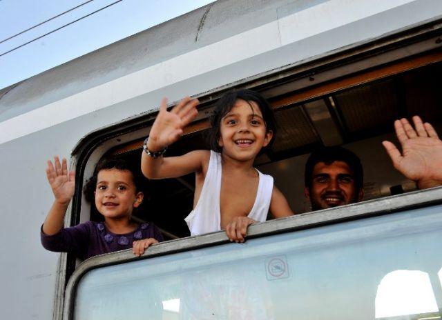 Niños migrantes saludan desde las ventanas de un tren después de subir en la estación en Llaca. Foto: REUTERS
