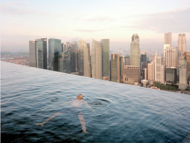 Un hombre nada en la piscina del piso 57 del Marina Bay Sands Hotel Atrás de él, se levanta el distrito financiero de Singapur. Paolo Woods y Gabriele Galimbert.