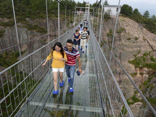 Turistas caminan sobre el puente colgante de cristal en el Geo-Parque Nacional Shiniuzhai en la provincia de Hunan, China. Foto: REUTERS