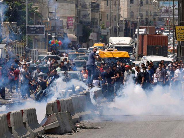 Palestinos manifestantes reaccionan a los gases lacrimógenos disparados por las tropas israelíes durante los enfrentamientos después de una protesta en solidaridad con los presos palestinos detenidos por Israel