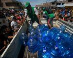 Trabajadores distribuyen agua embotellada en las zonas afectadas. | Foto: Reuters.