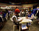 Funcionarios del CNE abrían desde primera hora de la mañana las más de 3.865 urnas impugnadas. Foto: AFP.