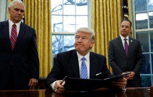 El presidente Donald Trump firma sus primeros decretos en el Salón Oval. Foto: REUTERS.