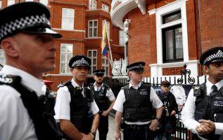 Oficiales de la policía británica se encuentran de servicio frente a la Embajada de Ecuador en Londres. Foto: AFP