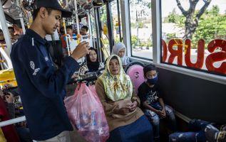 Un conductor de autobús recogiendo botellas de plástico usadas como pago de tarifa. Foto: AFP