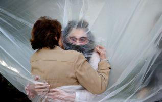 Nueva York.- Olivia Grant abraza a su abuela, Mary Grace Sileo, a través de una tela plástica colgada en una línea de ropa. Foto: AFP