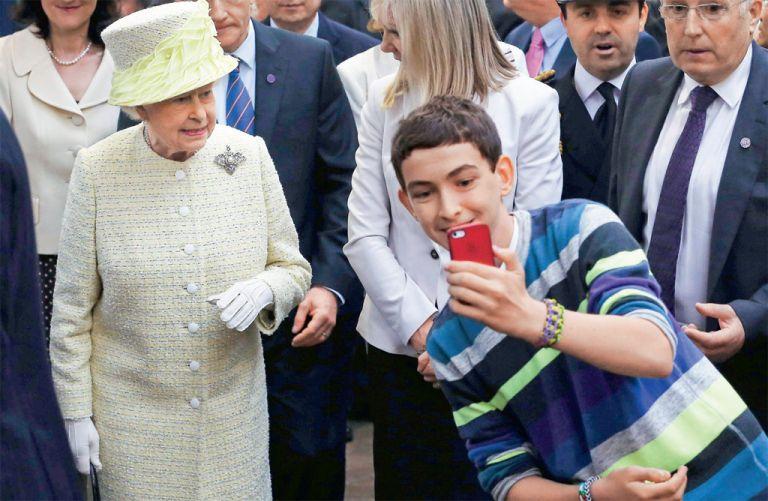 Un joven irlandés se toma un selfie frente a la reina Elizabeth de Reino Unido, durante una visita de la soberana a Belfast, Irlanda del Norte.