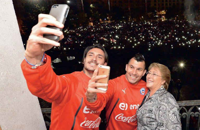 La presidenta chilena Michelle Bachelet se toma un selfie con los jugadores Gary Medel y Mauricio Pinilla.