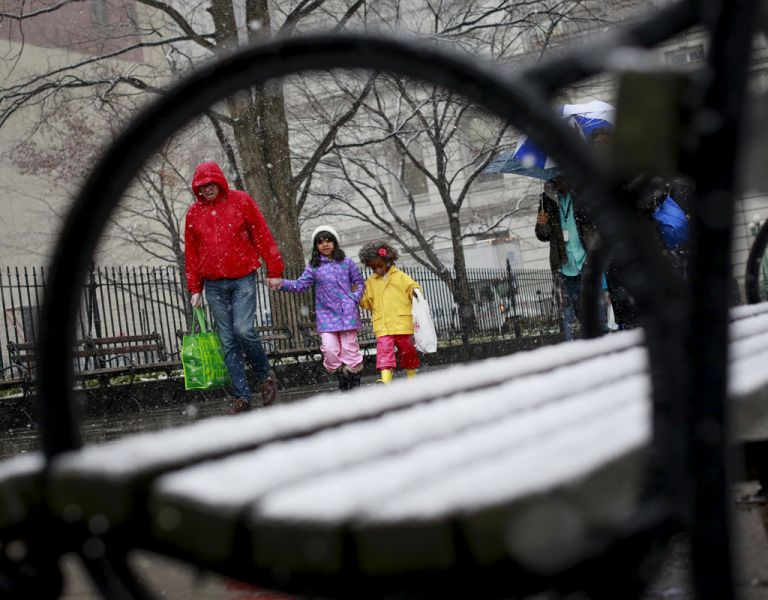 Un hombre camina junto a sus hijas en el City Hall Park de Nueva York durante las nevadas. Foto: REUTERS