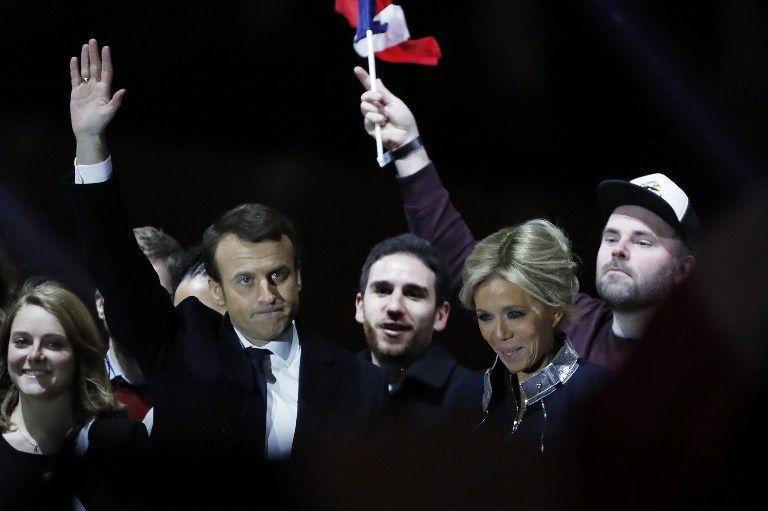 Emmanuel Macron, saluda con su esposa, Brigitte Trogneux, junto a Morgan Simon, un francés de 31 años que festeja con una bandera, el 7 de mayo. | Foto: Reuters.