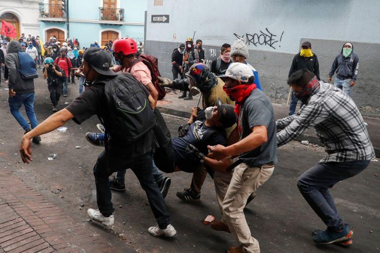 Entre varias personas llevan a un manifestante luego de ser afectado por gases lacrimógenos durante una protesta. Foto: Reuters