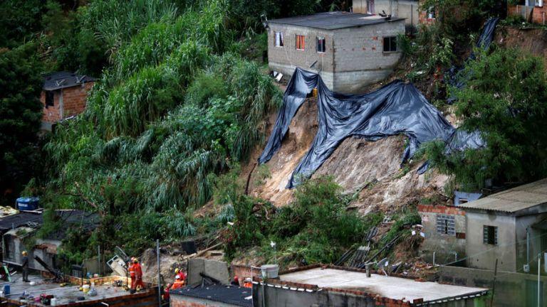 Equipos de rescate registran el sitio de un deslizamiento de tierra, luego de fuertes lluvias en el barrio Vila Ideal en Belo Horizonte, estado de Minas Gerais, Brasil.