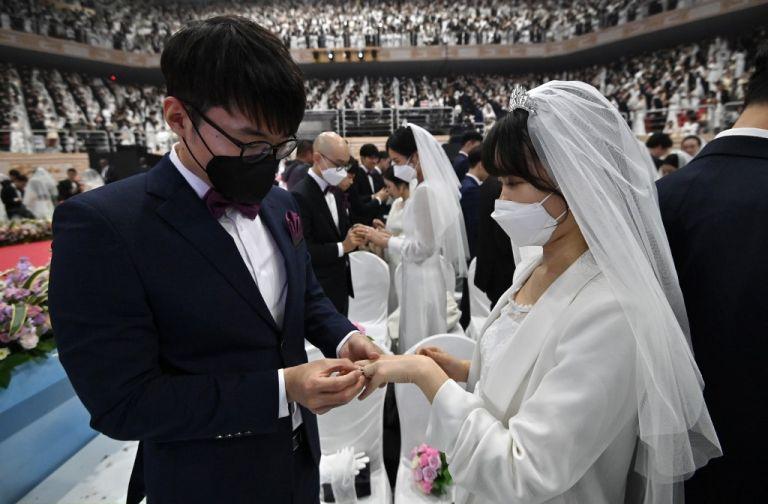 Las parejas con máscaras protectoras asisten a una ceremonia de boda masiva.  Foto: AFP