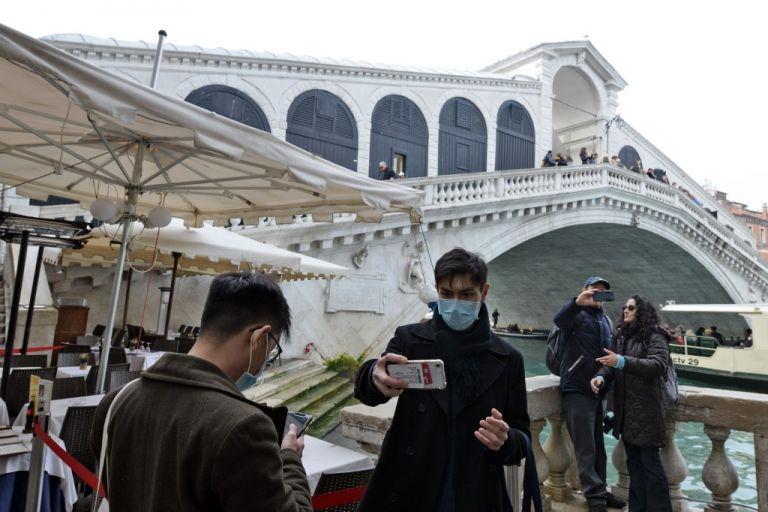 Los turistas posan para selfies frente al puente de Rialto en Venecia después de que el carnaval fue cancelado debido a un brote de coronavirus en Italia. Foto: AFP.