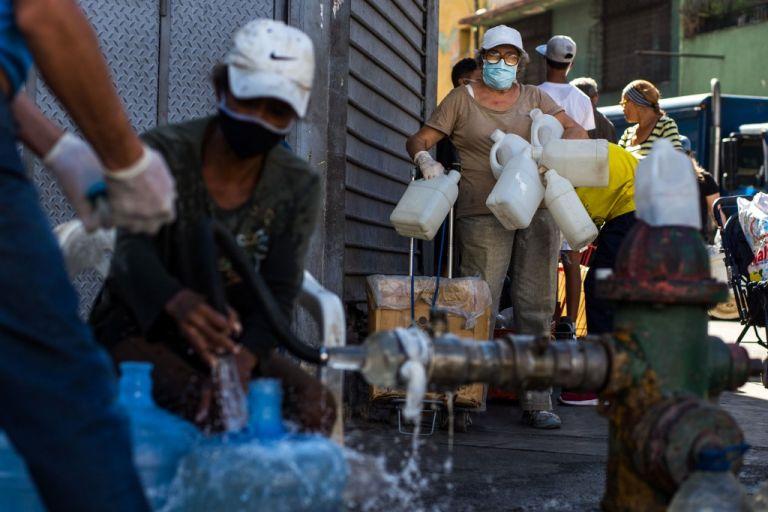Muchos caminan por calles desoladas con envases vacíos buscando agua. Foto: AFP