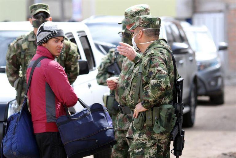 soldados colombianos hablando con un ciudadano que cruzó desde Ecuador hacía Colombia por el río Blanco en Colombia en Altamira. Foto: EFE