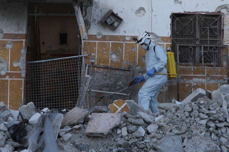 """Personal de defensa sirio, conocido como """"Cascos Blancos"""" por su nuevo traje de bioseguridad, realiza labores de limpieza en zonas destruidas por el conflicto. Ni la pandemia detiene la crisis siria."""