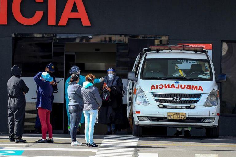 Familiares de pacientes diagnosticados con la COVID-19 esperan información en el hospital del Iess, en Quito. Foto: EFE