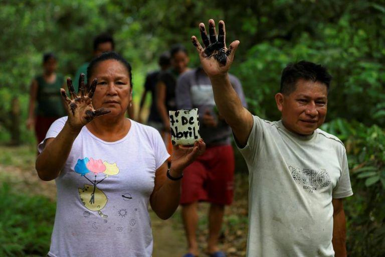 Indígenas de la comunidad de Amarumesa muestran residuos de petróleo en sus manos. Foto: EFE.