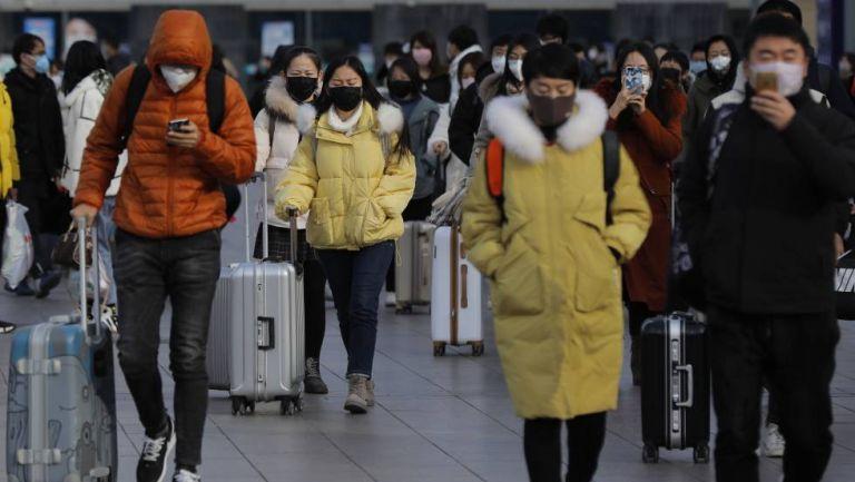 Un grupo de personas con mascarilla salen de la estación de tren de Pekín.Foto:EFE