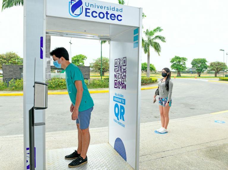 En la entrada de la Universidad Ecotec se colocó un termómetro automático digital. De pasar ese filtro, el estudiante debe escanear un código QR que le habilita el ingreso al campus. Foto: César Mera.