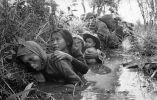 Un grupo de mujeres y niños que se refugian del fuego cerca de Saigón.