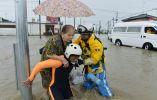 Una mujer es rescatada por agentes de policía en una zona residencial inundada por el río Kinugawa. Foto: REUTERS.