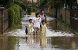 Una familia camina a través de una zona residencial inundada por el río Kinugawa. Foto: REUTERS.