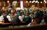 Gente en ropa tradicional de Baviera se toman un descanso después del desfile de Oktoberfest en Munich. Foto: REUTERS
