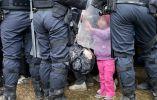 Una niña toca el escudo antidisturbios de la policía mientras que ella y otros migrantes a pie cruzan la frontera en Rigonce. Foto: REUTERS