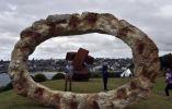 Los turistas fotografían la obra de Peter Lundberg, una de las esculturas expuestas en el paseo marítimo de Bondi, Sidney (Australia). AFP