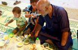 """Un niño iraquí ayuda a su padre discapacitado a interrumpir su ayuno durante una """"cena de ayuno"""". Foto: Reuters"""